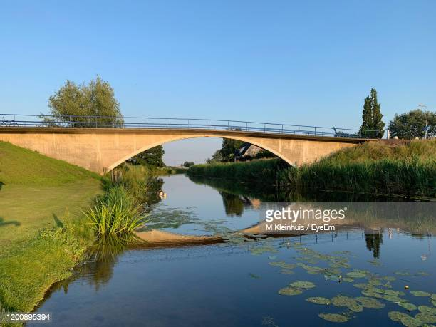 arch bridge over river against clear blue sky - overijssel stock pictures, royalty-free photos & images