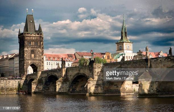 arch bridge over river against cloudy sky - charles bridge stock pictures, royalty-free photos & images