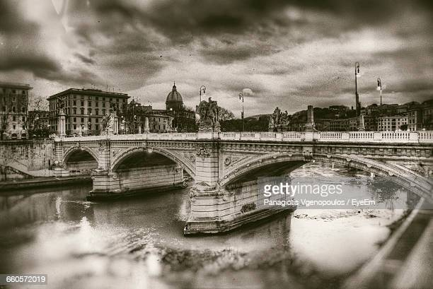 arch bridge over river against cloudy sky - vgenopoulos stock pictures, royalty-free photos & images