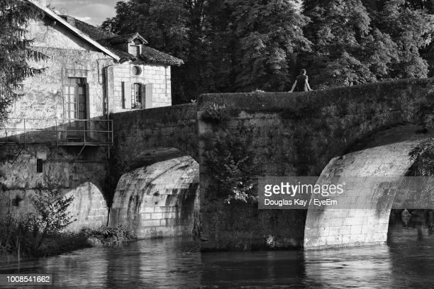 Arch Bridge Over River Against Old Building