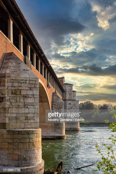 arch bridge over river against sky during sunset - イタリア パヴィア ストックフォトと画像