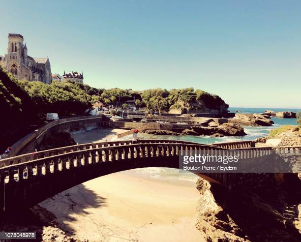 arch bridge over river against sky in city - biarritz stock pictures, royalty-free photos & images