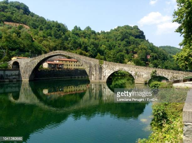 arch bridge over river against sky - loredana perugini stock pictures, royalty-free photos & images