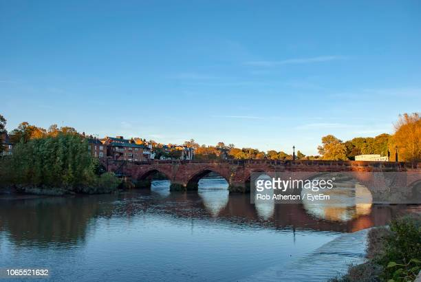 arch bridge over river against sky - chester england stock pictures, royalty-free photos & images