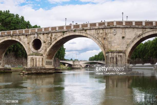 arch bridge over river against sky - marek stefunko stock photos and pictures