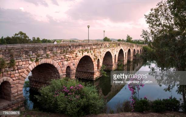 arch bridge over river against sky - segovia stock photos and pictures