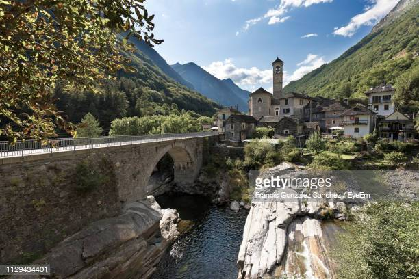 arch bridge over river amidst buildings against sky - ticino canton stock pictures, royalty-free photos & images