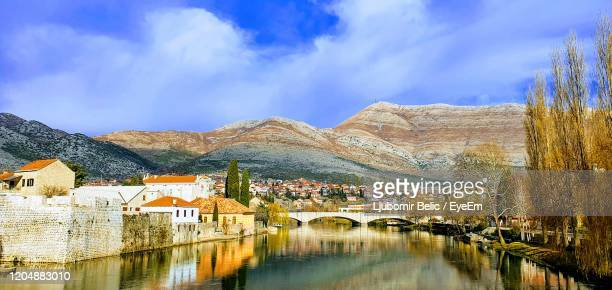 arch bridge over river amidst buildings against sky - ljubomir belic stock pictures, royalty-free photos & images