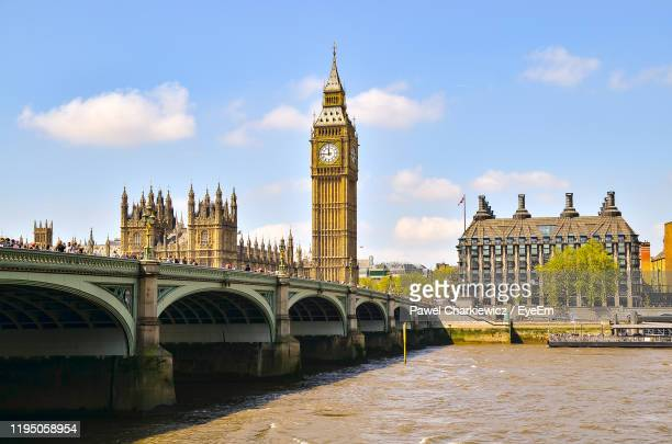 arch bridge over river and buildings against sky in city - day stock pictures, royalty-free photos & images