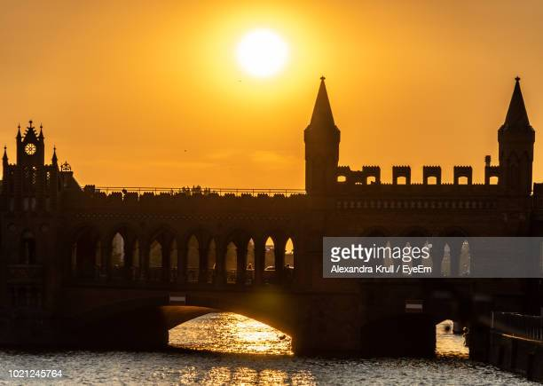 Arch Bridge Over River By Buildings Against Sky During Sunset