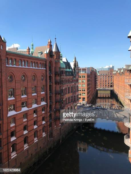 arch bridge over river by buildings against sky in city - krings stock pictures, royalty-free photos & images