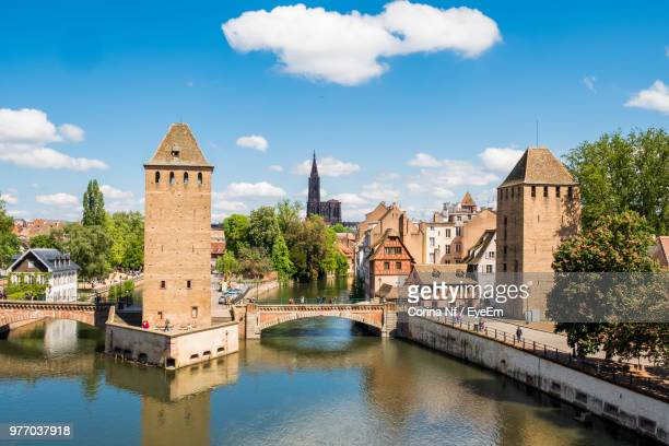 arch bridge over river by buildings against sky in city - strasbourg stock pictures, royalty-free photos & images
