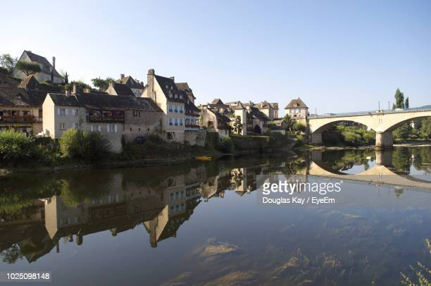 arch bridge over river by buildings against sky - correze stock pictures, royalty-free photos & images