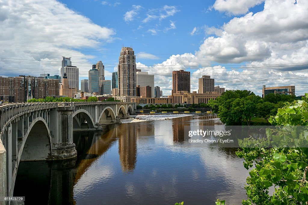 Arch Bridge Over River By Buildings Against Sky : ストックフォト