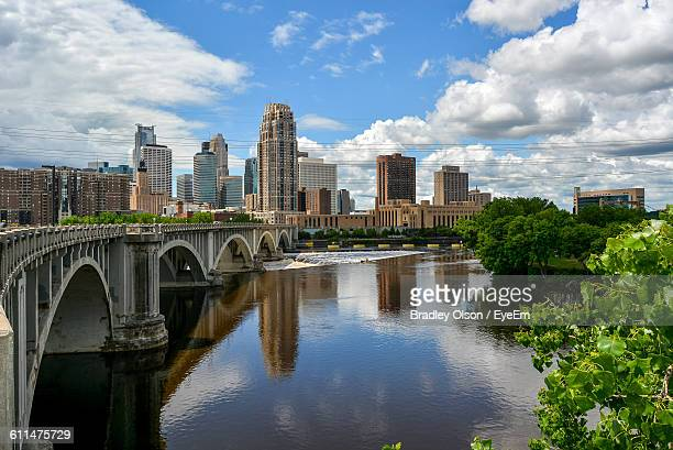arch bridge over river by buildings against sky - minnesota foto e immagini stock