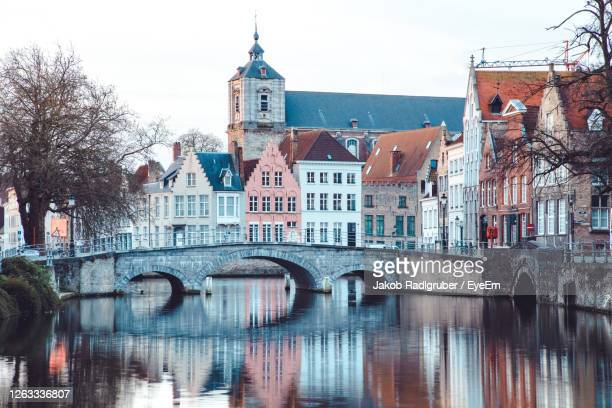 arch bridge over river by buildings in city against sky - belgium stock pictures, royalty-free photos & images