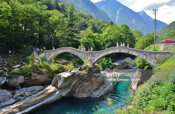 arch bridge over river by trees against sky - locarno stock photos and pictures