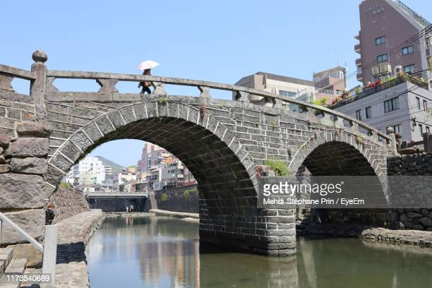 arch bridge over river in city against clear sky - 建築上の特徴 アーチ ストックフォトと画像