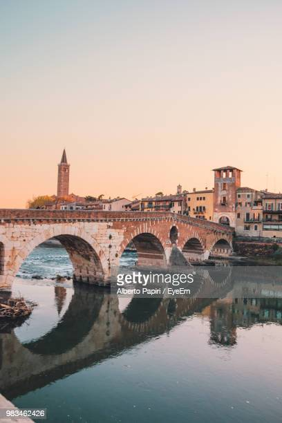 arch bridge over river in city against clear sky - イタリア ヴェローナ ストックフォトと画像