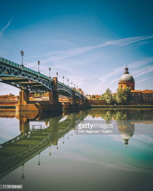 arch bridge over river in city against sky - toulouse stock pictures, royalty-free photos & images