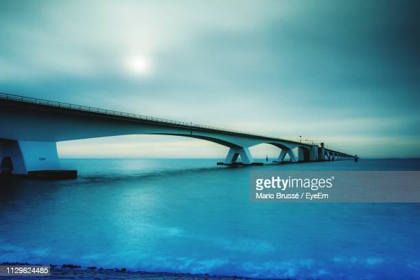 arch bridge over sea against sky - zeeland stock pictures, royalty-free photos & images