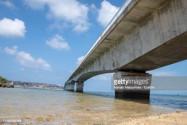arch bridge over sea against sky - naruto stock photos and pictures