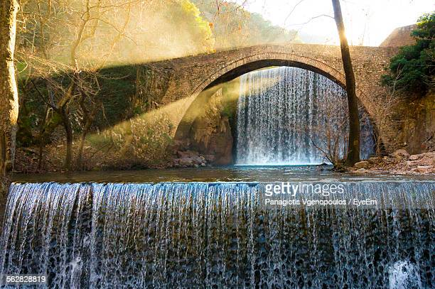 arch bridge over stream - vgenopoulos stock pictures, royalty-free photos & images