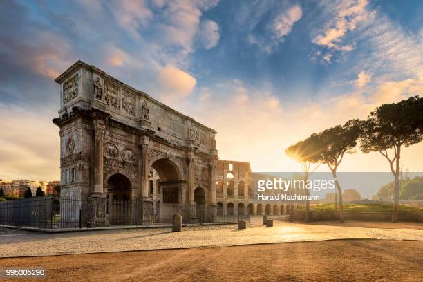 arch of constantine with the colosseum in the background at sunrise, rome, lazio, italy - roma stock photos and pictures