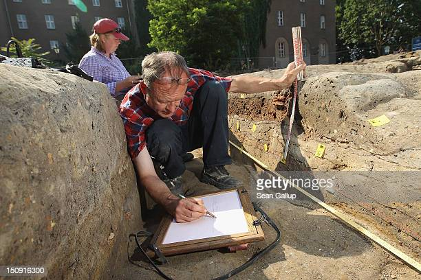 Archaeological draftsman Ralf Scherrer draws the layers of residue and earth at the Grosser Juedenhof archaeological excavation site as archaeologist...