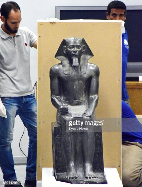 Archaeological experts carefully move a statue of King Khafre transported from an archaeological museum in Cairo on Sept 20 at a restoration center...