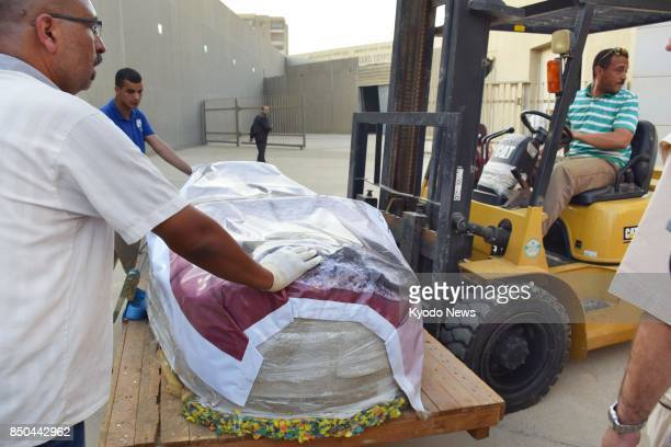 Archaeological experts carefully move a statue of King Khafre which has been wrapped for protection from an archaeological museum in Cairo to the new...