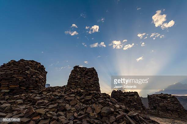 Dawn sun rays rise over ancient handmade stone burial mounds and tombs atop a desert ridge.