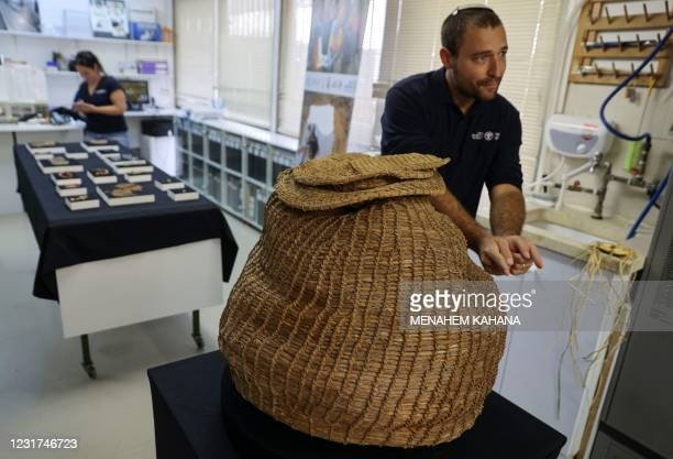 Archaeologist at the Israel Antiquities Authority Haim Cohen shows a 10500-year-old basket dating back to the Neolithic period that was unearthed in...