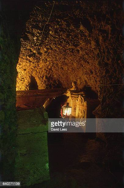 Archaeologist inspecting an Etruscan ash urn in situ in the tomb of Cutu Perugia Italy