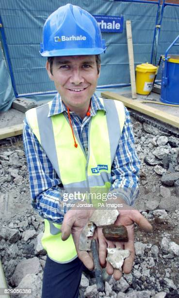 Archaeologist Mark Kirby holds parts of a Hurricane plane which include a part of the engine block a piece of the wooden tail fin fragments of the...