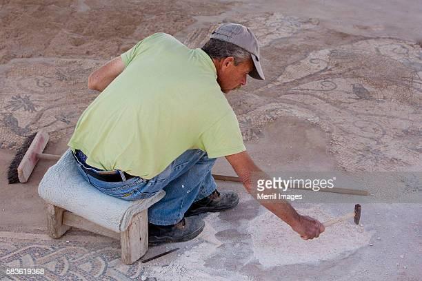 archaeologist restoring Ancient Roman mosaic at Caesarea
