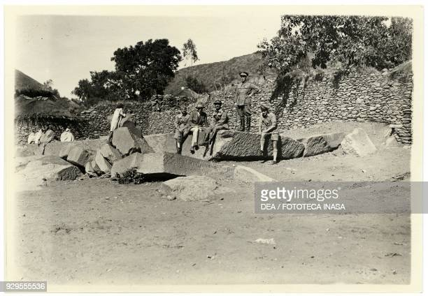 Archaeologist Ugo Monneret de Villard with some Italian soldiers sitting on broken stele Axum Ethiopia photograph by Ugo Monneret de Villard 1937
