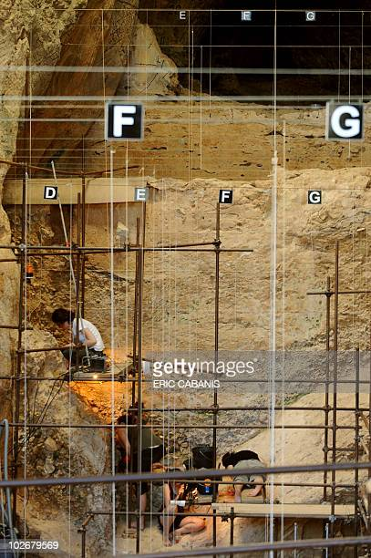 Archaeologists are seen inside the Caune de l'Arago cave near Tautavel southwestern France on July 6 2010 during excavation works Henry de Lumley and...