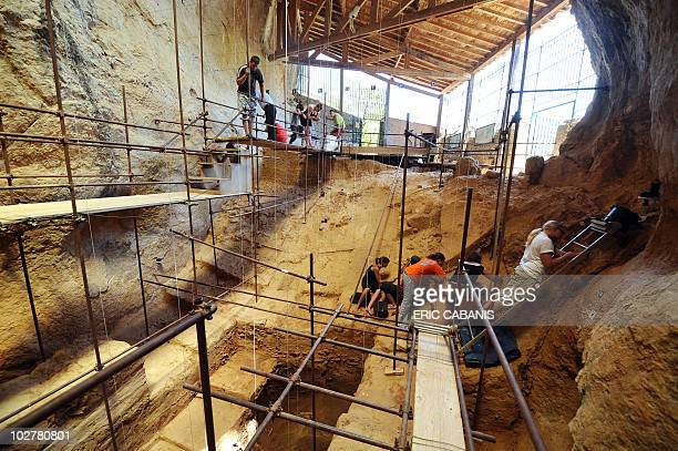 Archaeologists are seen inside the Caune de l'Arago cave near Tautavel southwestern France on July 6 2010 during excavation works French prehistorian...