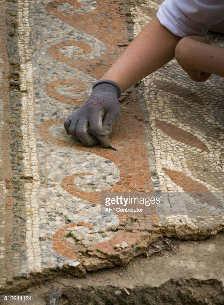 Archaeologists from Inrap excavate mosaics at an archaeological site from the GalloRoman era on July 11 2017 in Auch / AFP PHOTO / Eric CABANIS
