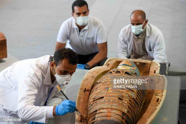 Archaeologists inspect a mummy, wrapped in a burial shroud adorned with brightly coloured hieroglyphic pictorials, during the unveiling of an ancient...