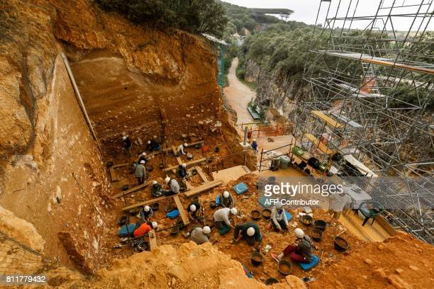 Archaeologists work at the 'Gran Dolina' dig in the archaeological site of the Atapuerca mountain range province of Burgos on July 10 2017 Fossils...