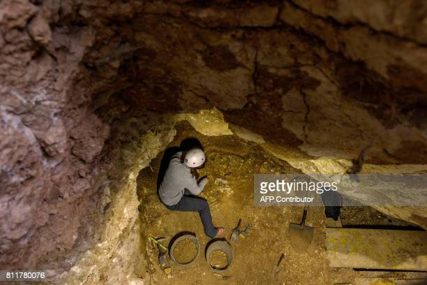 Archaeologists work at the 'Sima del Elefante' dig in the archaeological site of the Atapuerca mountain range province of Burgos on July 10 2017...