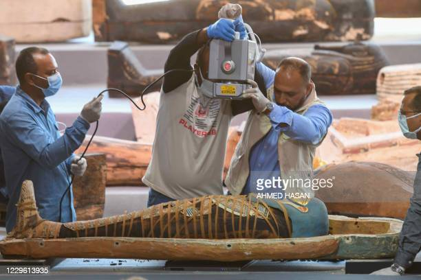 Archaeologists xray a mummy wrapped in a burial shroud adorned with brightly coloured hieroglyphic pictorials during the unveiling of an ancient...