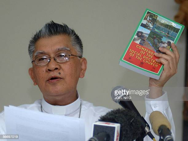 Archbishop Angel Lagdameoarchdiocese of Jaro Catholic Bishops Conference of the Philippines president shows a book of Catholic churces social...