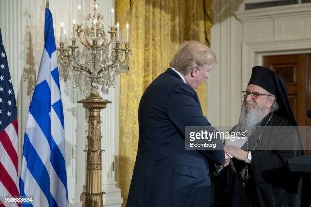 Archbishop Demetrios of America elder archbishop of the Greek Orthodox Archdiocese of America right shakes hands with US President Donald Trump...