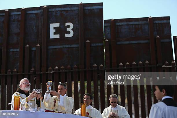 Archbishop of Boston Cardinal Sean O'Malley celebrates communion next to the USMexico border fence during a special 'Mass on the Border' on April 1...
