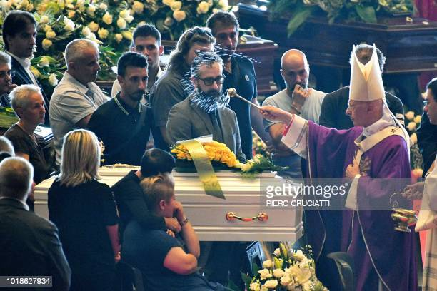 TOPSHOT Archbishop of Genoa Cardinal Angelo Bagnasco blesses the coffins during the state funeral of the victims of the Morandi Bridge collapse in...