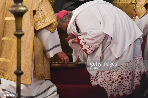 Archbishop of Krakow Marek Jedraszewski kisses a feet of a man after washing of the feet ritual during the Holy Thursday Mass at Wawel Royal...