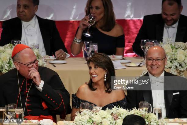 Archbishop of New York Cardinal Timothy Dolan talks with US Ambassador to the United Nations Nikki Haley as her husband Michael Haley looks on during...